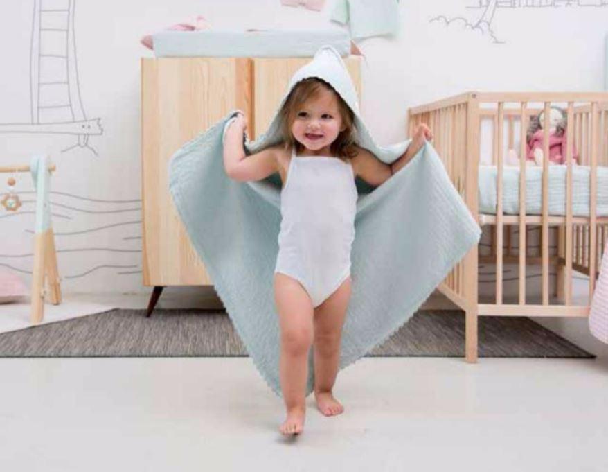 Koeka blauw wiegdeken en koeka onesies babykleding met gehuurde wieg op de achtergrond